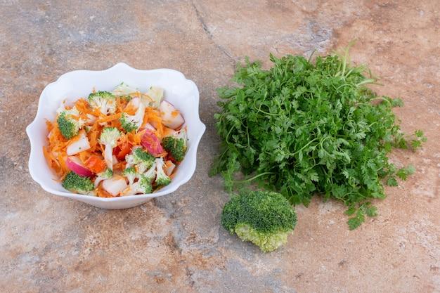 Korianderbündel, brokkoli und platte mit gemischtem gemüsesalat auf marmoroberfläche