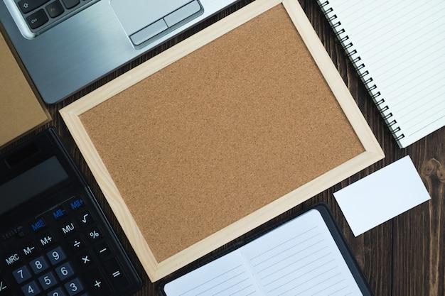 Korkbrett, taschenrechner und notizbuch auf dem tisch