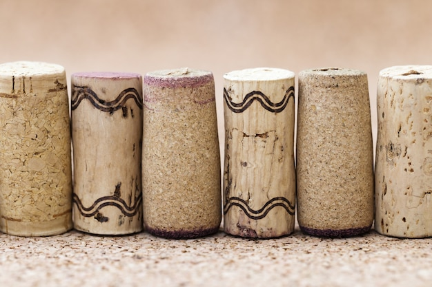 Korken aus der nahaufnahme von weinflaschen werden in einer reihe auf einem unscharfen hölzernen hintergrund mit platz für text gebaut