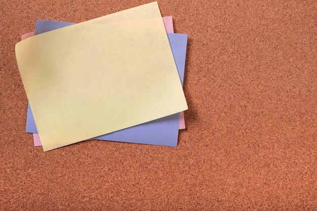 Korken-hintergrund-kopienraum der gelben klebrigen beitragsnotiz verschiedene