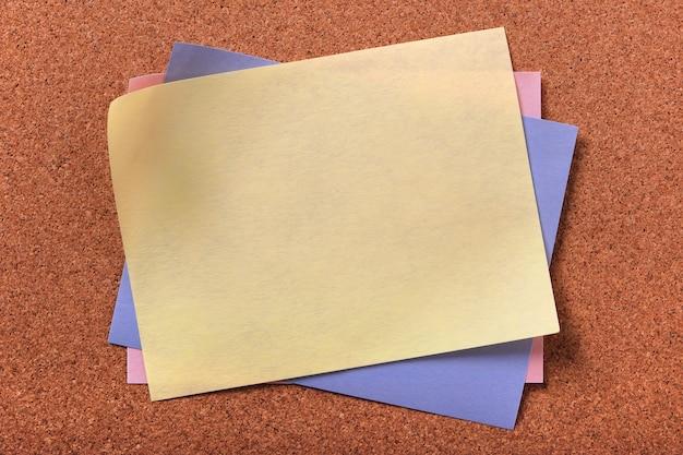 Korkenhintergrund der gelben klebrigen postanmerkung verschiedene farben