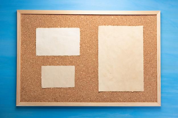 Korkplatte und memory-papier auf hölzerner hintergrundtextur
