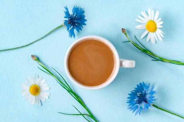 Kornblumen, kamille und eine tasse heißen kaffee. ansicht von oben