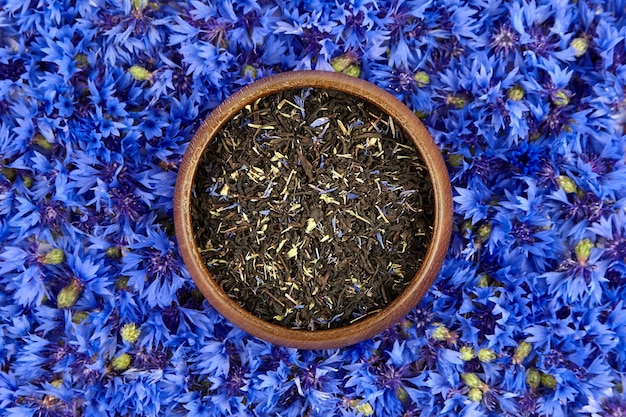 Kornblumen mit schwarzer teemischung in einer hölzernen schüssel auf blauem blumenhintergrund, draufsicht. kräutertee