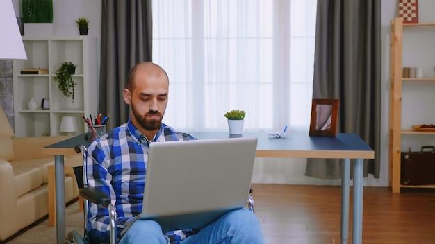 Korporatist im rollstuhl, der vom homeoffice aus am laptop arbeitet.