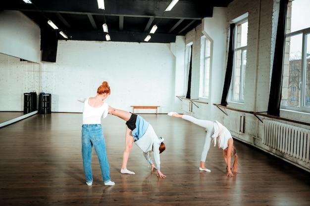 Korrekte position. die rothaarige tanzlehrerin trägt blue jeans und korrigiert die beinposition ihres schülers