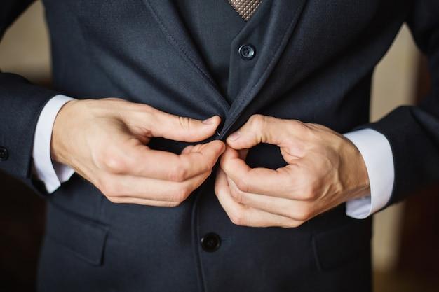 Korrigieren sie den knopf an der jacke, die nahaufnahme der hände, das anziehen, den stil des mannes, korrigieren sie die ärmel und bereiten sie sich auf die hochzeit vor
