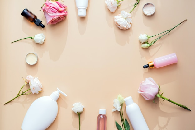 Kosmetik aus natürlichen inhaltsstoffen und extrakten aus blumen und rosen auf beigem hintergrund