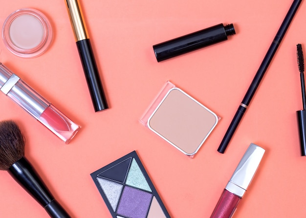 Kosmetik fiel auf korallenrotem hintergrund aus der kosmetiktasche
