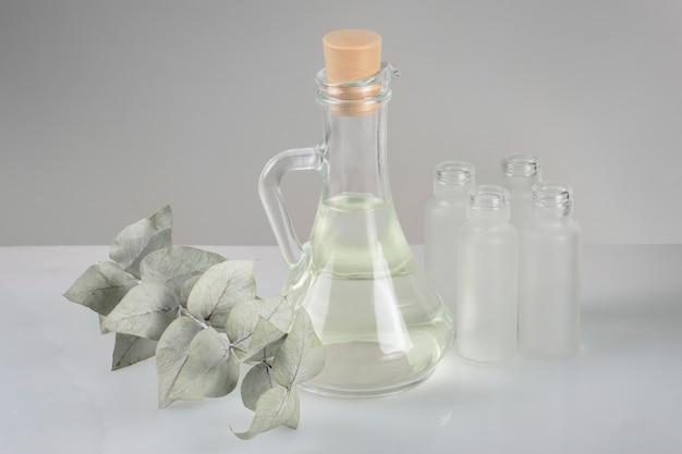 Kosmetik für zu hause gemacht. tonic, kräutertinktur, apothekenflaschen und grüner zweig