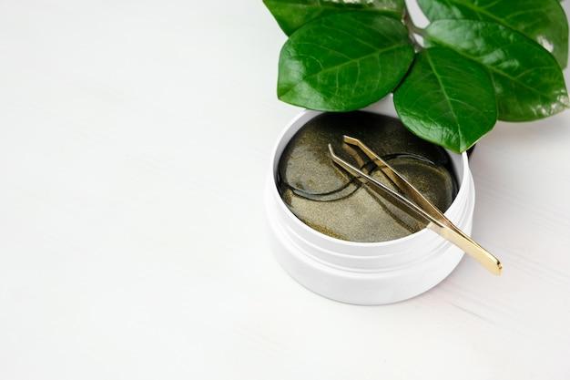Kosmetik-hydrogel-augenklappen und grüner zweig mit blättern auf einem weißen hintergrund mit kopienraum. hautpflege- und kosmetikkonzept. anheben der anti-falten-kollagenmaske.