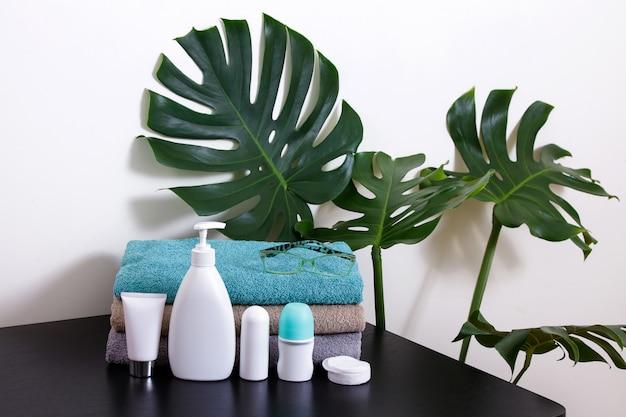 Kosmetik in weißen röhren und badezusätzen auf einem schwarzen tisch mit tropischen blättern.