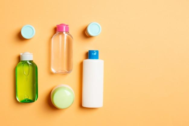 Kosmetik-spa-branding-mock-up, draufsicht mit kopienraum. set aus tuben und gläsern mit sahne flach auf farbigem hintergrund.