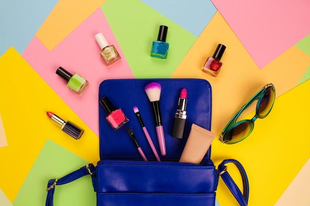 Kosmetik und accessoires für frauen fielen aus der blauen handtasche