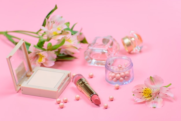 Kosmetik und blumen auf einem rosa hintergrund