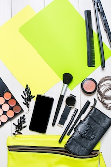 Kosmetik und damenaccessoires fielen aus der grünen handtasche auf weißem hintergrund