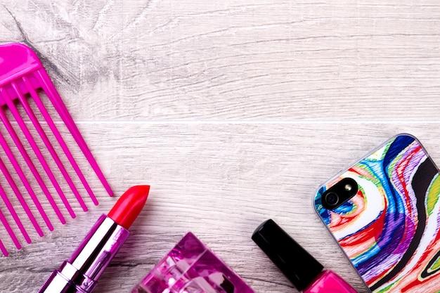 Kosmetik und handy. make-up-produkte auf holzhintergrund. heben sie sich durch stil hervor. glänzender look für den alltag.