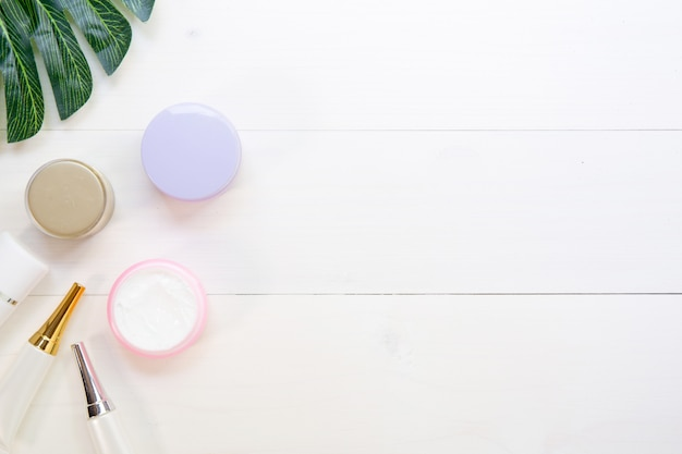 Kosmetik und hautpflegeprodukt und grünblätter auf weißer hölzerner tabelle