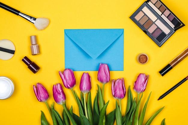 Kosmetik und rosa tulpen an gelber wand
