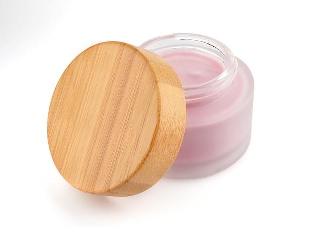 Kosmetikbehälter mit creme mit einem holzdeckel auf einer weißen oberfläche. glas für hautpflegeprodukte.