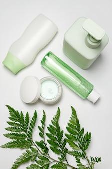 Kosmetikbehälter mit grünen kräuterblättern, leere etikettenverpackung für das branding. feuchtigkeitscreme, shampoo, tonic, gesichts- und körperhautpflege.