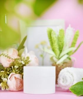 Kosmetikcremebehälter mit rosa lilienblüten