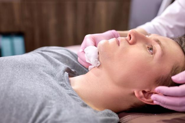 Kosmetiker arzt wischen männlichen patienten gesicht nach der maske, kosmetische schönheitsverfahren im spa-salon.