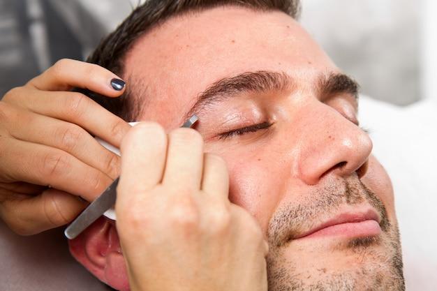 Kosmetiker, der augenbrauen eines schönen mannes mit pinzette in einem schönheitssalon zupft