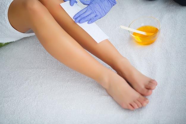Kosmetiker, der das bein der frau im badekurortsalon einwächst