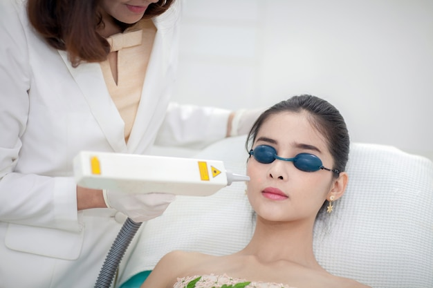 Kosmetiker, der dem gesicht der jungen frau laser-epilations-behandlung gibt