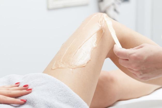 Kosmetiker, der haar der jungen frau mit laser entfernt