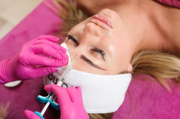 Kosmetikerarzt hände, die schönheitsverfahren zum weiblichen gesicht mit spritze tun. kosmetische medizin und chirurgie, schönheitsinjektionskonzept