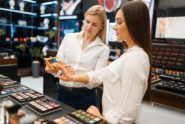 Kosmetikerin an der theke und frau im kosmetikgeschäft. luxus-schönheitssalon, kundin und kosmetikerin im modegeschäft