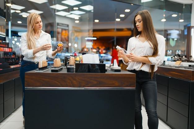 Kosmetikerin an der theke und frau im kosmetikgeschäft. luxus-schönheitssalon, kundin und kosmetikerin im modemarkt