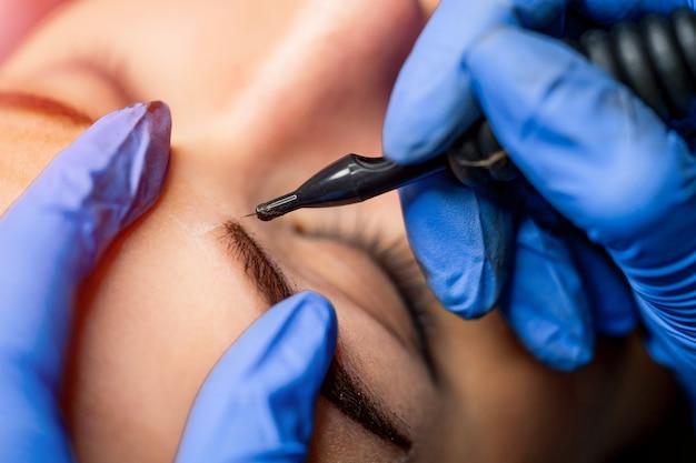 Kosmetikerin arbeiten, machen permanent make-up im beauty-salon. kosmetikerin, die dauerhafte verfassung der augenbrauen bildet.