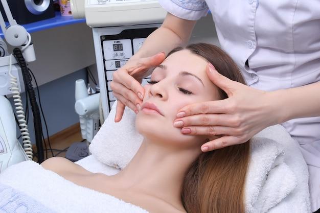 Kosmetikerin arbeitet im schönheitssalon. sie macht eine gesichtsmassage mit akzent am hals