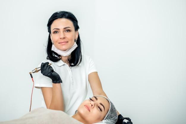 Kosmetikerin arbeitet während der wimpernverlängerung mit dem patienten