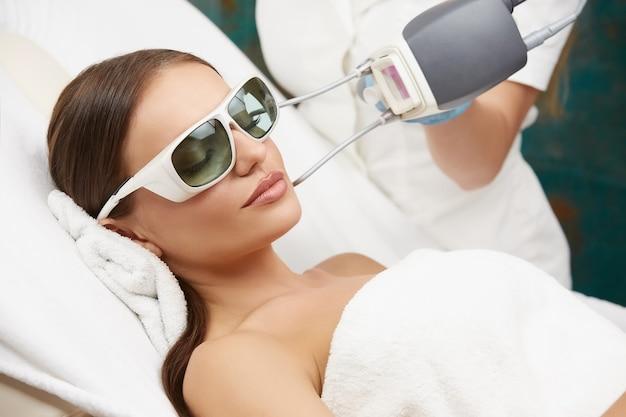Kosmetikerin beim entfernen von gefäßen auf schönem frauengesicht im luxus-spa-salon, hübsche frau, die gesichtstherapie im schönheitssalon erhält
