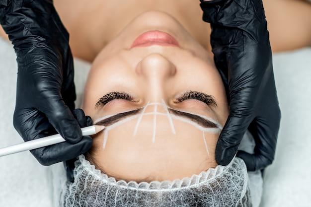 Kosmetikerin beim tätowieren von augenbrauen, die permanentes make-up trinken.