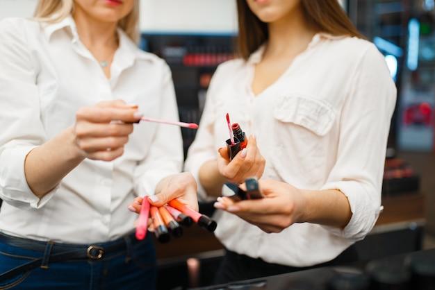 Kosmetikerin berät frau an der vitrine im kosmetikgeschäft. luxus-schönheitssalon, kundin und kosmetikerin im modemarkt