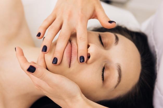 Kosmetikerin berührt mädchen gesicht gesichtsreinigung mit professioneller kosmetischer gesichtsmassage