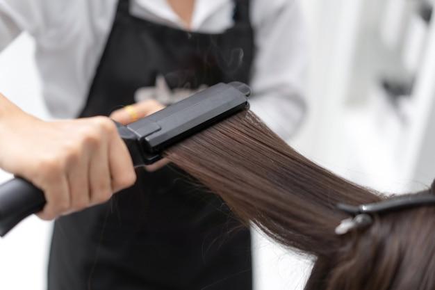 Kosmetikerin bügelt haarkunden