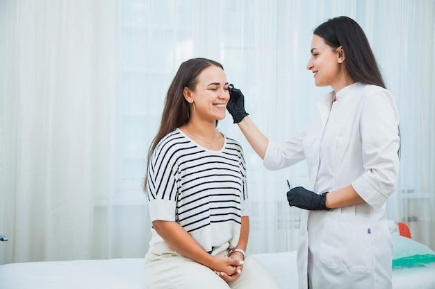 Kosmetikerin, die augenbrauen mit speziellen instrumenten korrigiert. junge frau, die schönheitsgesichtsverfahren macht.