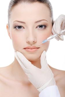 Kosmetikerin, die botox auf weibliche lippen injiziert
