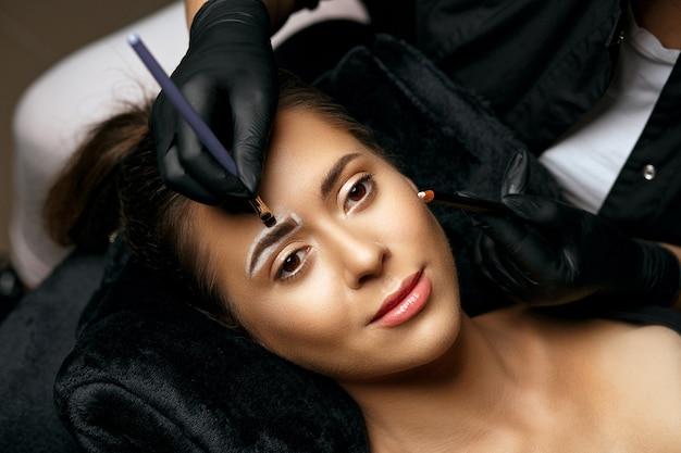 Kosmetikerin, die brauen für ein permanentes make-up mit puder vorbereitet. weißen stift um die brauen auftragen