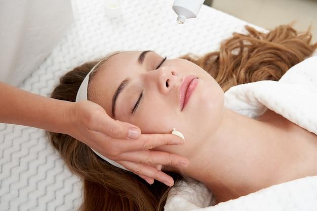 Kosmetikerin, die creme auf weibliches gesicht aufträgt frau, die eine gesichtsbehandlung im spa-salon hat