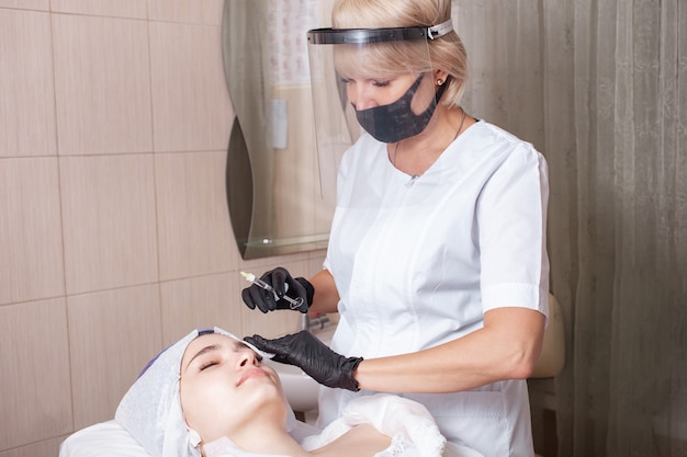 Kosmetikerin, die das verfahren der mesotherapie am klienten durchführt