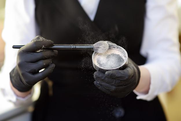 Kosmetikerin, die den grundton mit einem speziellen pinsel aufträgt. gesichtspflege und make-up
