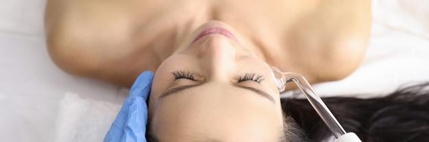Kosmetikerin, die der jungen frau im schönheitssalon das darsonval-verfahren gibt. physiotherapie in der kosmetik und dermatologie konzept