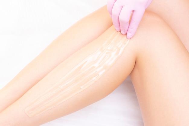Kosmetikerin, die die beine der jungen frau mit flüssigem zucker im kurzentrum enthaart.